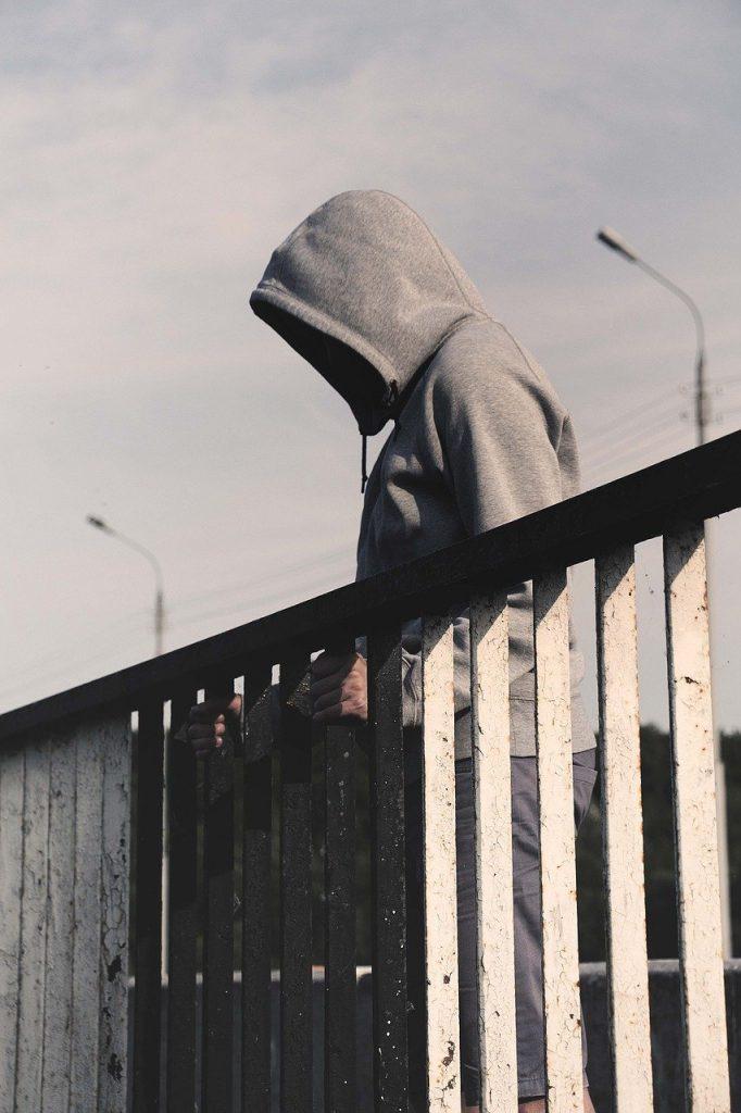 hooded man looking down from bridge